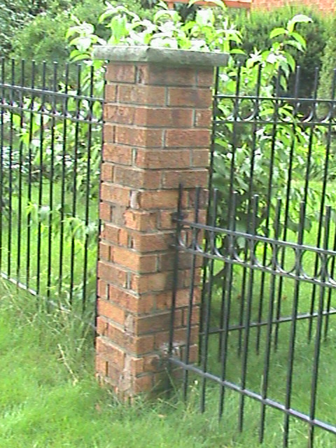 Brick post in front yard of home at the end of metal fence.