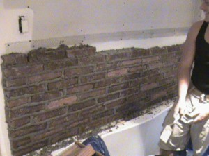Masonry workers laying brick in bathroom.