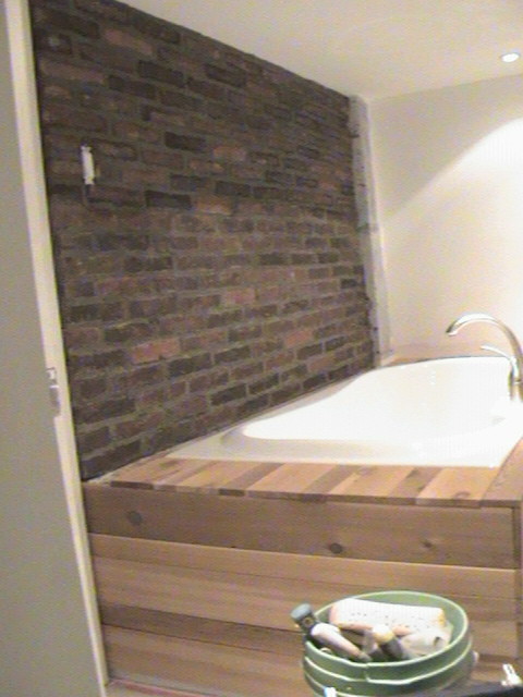Beautiful brick wall in bathroom behind bath tub.