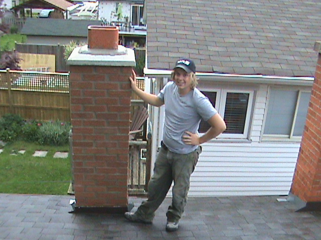 Clint Turnbull standing in front of repaired chimney.